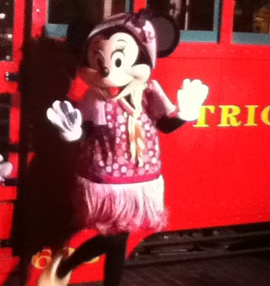Minnie Mouse in her Newsy Flapper Outfit in front of the trolley carat California Adventure